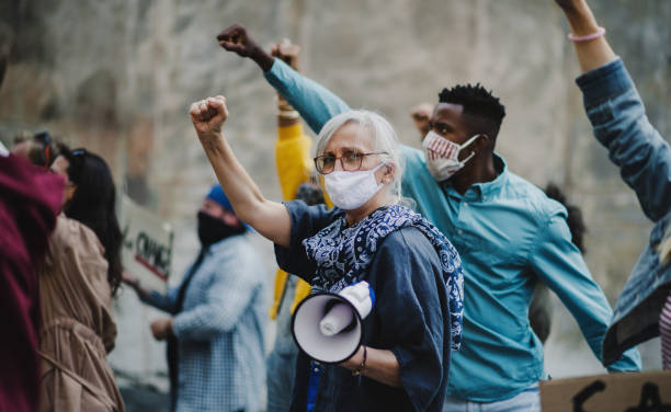 Group of people activists with raised fists protesting on streets, protests demonstration and coronavirus concept. stock photo