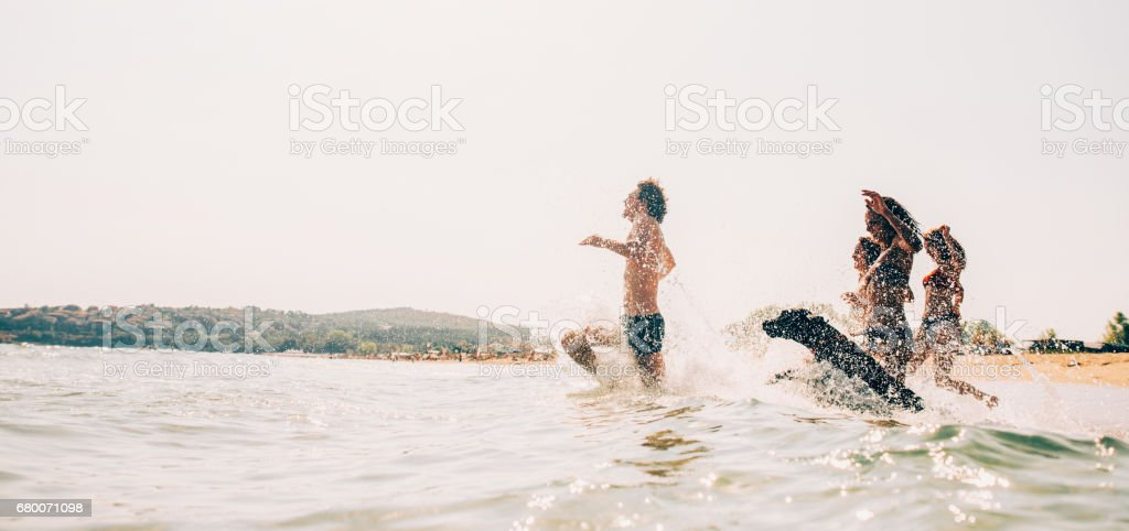 Group of people and a dog swimming in the sea stock photo