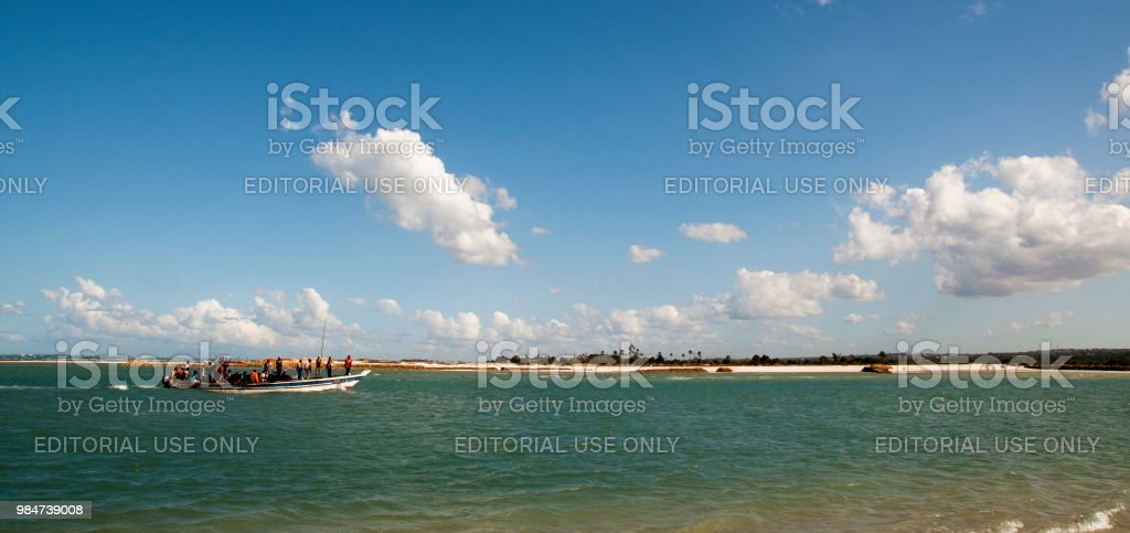 A group of people are ferried from nearest islands to Dar es Salaam through a ferry boat amidst the waterways created by Indian Ocean. stock photo