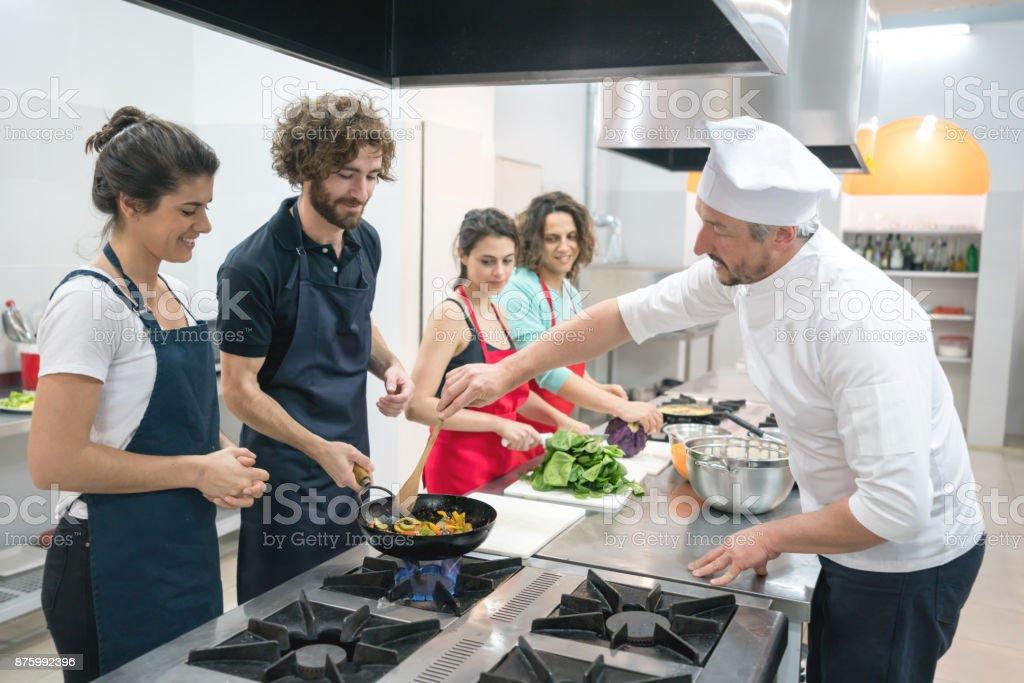 Gruppe von Menschen auf eine Küche Klasse und Koch lehrt sie, wie Sie Sautieren Sie das Gemüse im Wok – Foto