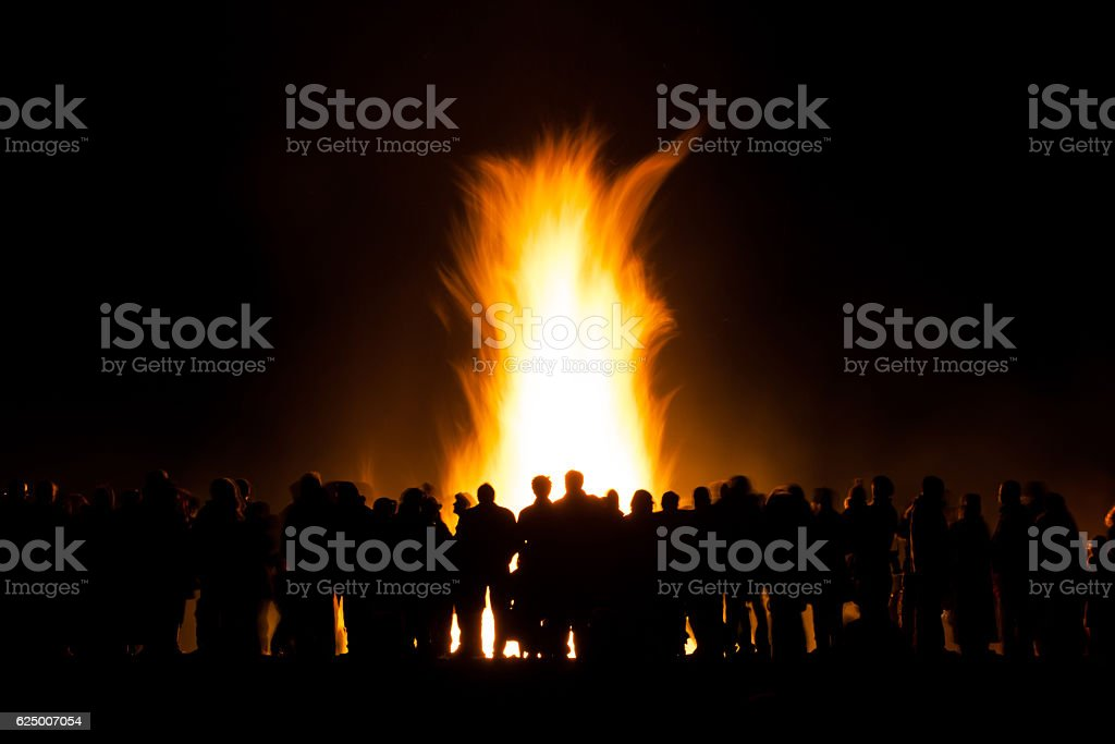 group of people at bonfire stock photo