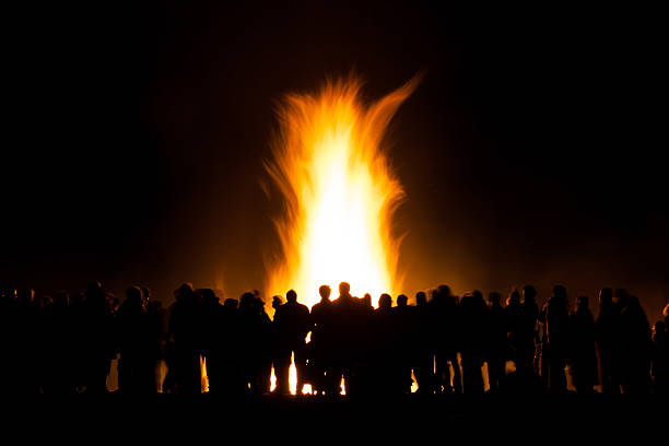 group of people at bonfire Long exposure of people watching a bonfire at night, slight motion blur to people and the fire bonfire stock pictures, royalty-free photos & images
