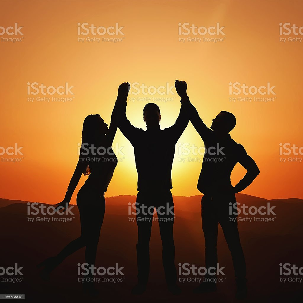 Group of people at sunset rejoices victory stock photo