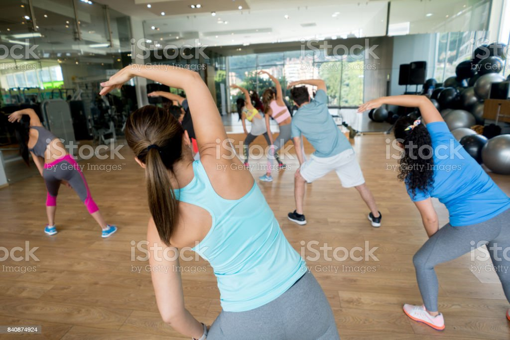 Rear view of a group of people at the gym in an aerobics class -...