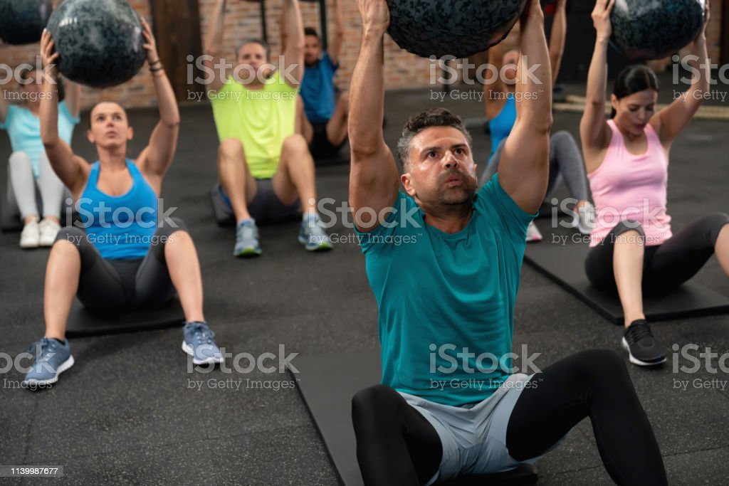 Group of people at the gym in class doing abs with a fitness ball all...
