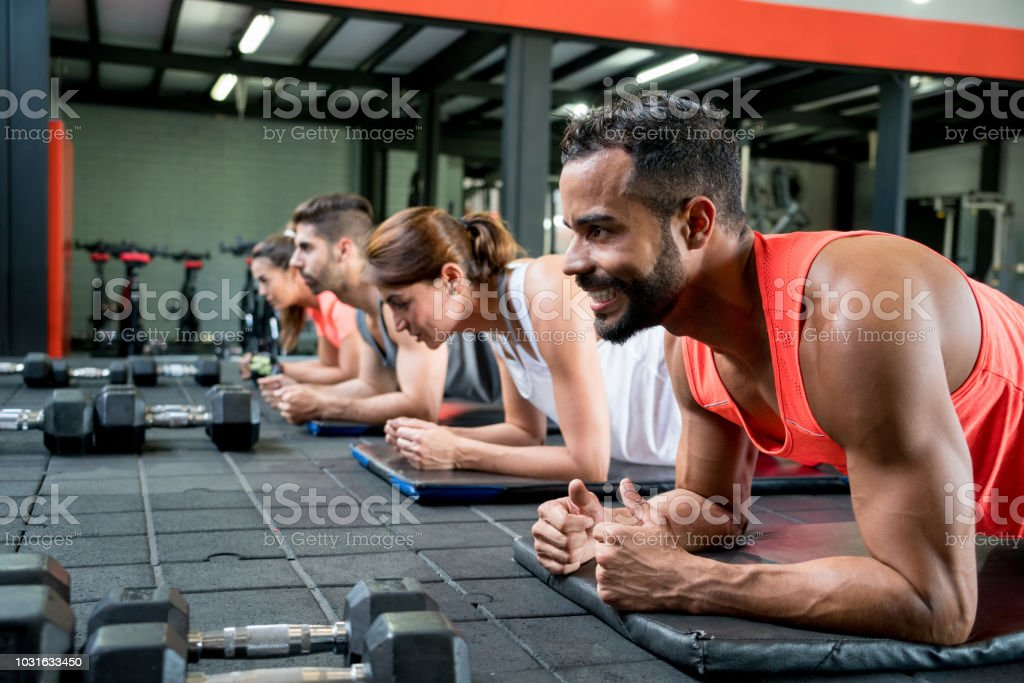 Group of people at the gym in class doing planks on an exercise mat...