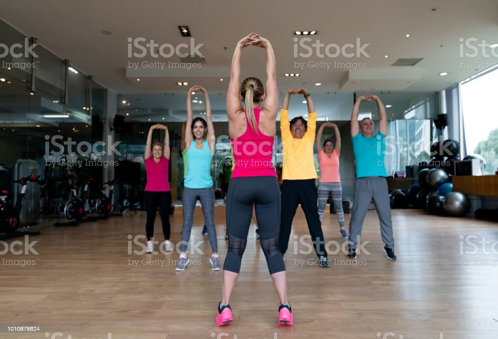 Group of people at the gym stretching in an aerobics class and...