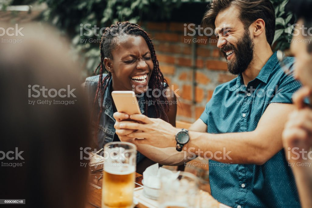 Group of people at the restaurant is laughing at the photo from the phone stock photo