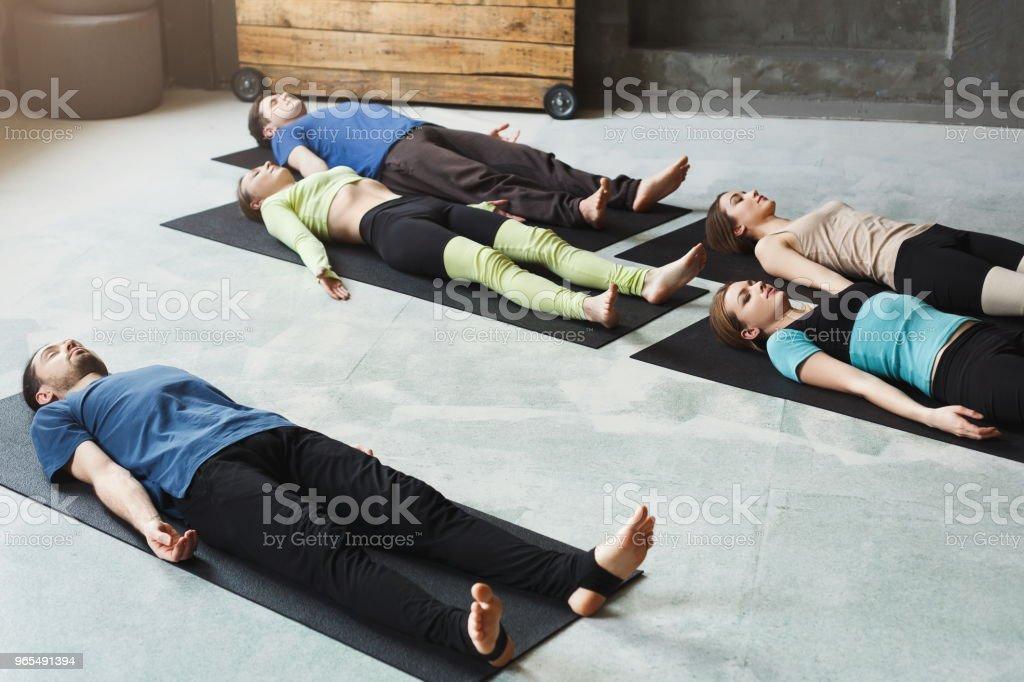 Gruppe Von Menschen Bei Yogakurs Nach Ubungen Am Boden Liegend Stock
