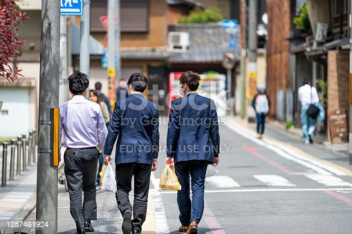 Kyoto, Japan - April 17, 2019: Group of people business salaryman walking in suit back for lunch holding store bought food in plastic bags on street road