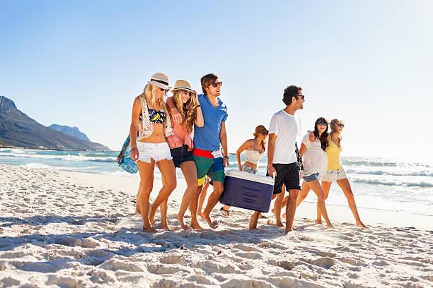 group of people carrying cooler to party on beach - strandfeest stockfoto's en -beelden