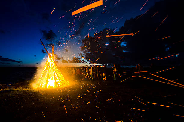 Group of people celebrating June solstice at the bonfire stock photo