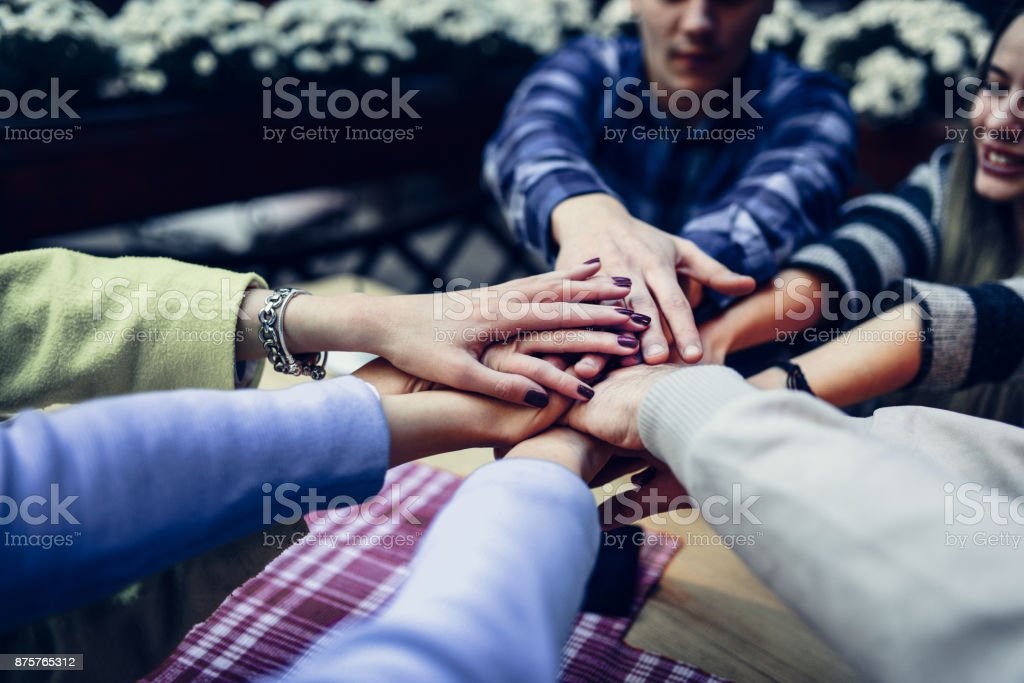 Group of People Celebrating With Hands In the Middle stock photo