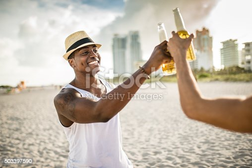 istock group of people cheering beers at dusk on the beach 503397590