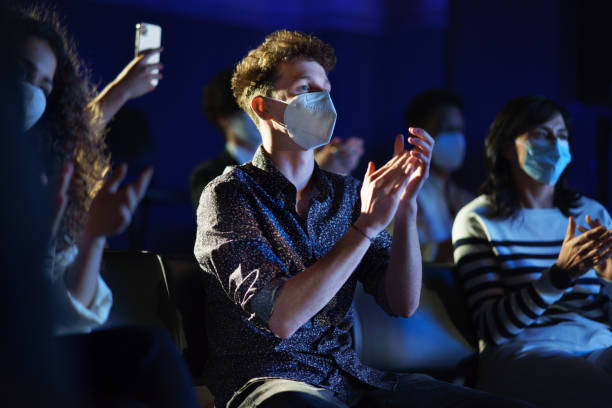 Group of people clapping while listening to presentation at conference, coronavirus concept. stock photo