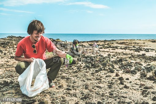 Group of people cleaning the beach from plastic and rubbish - Volunteers at work for garbage coast side problem - Environmental, pollution and ecolosystem warning concept - Focus on  guy body