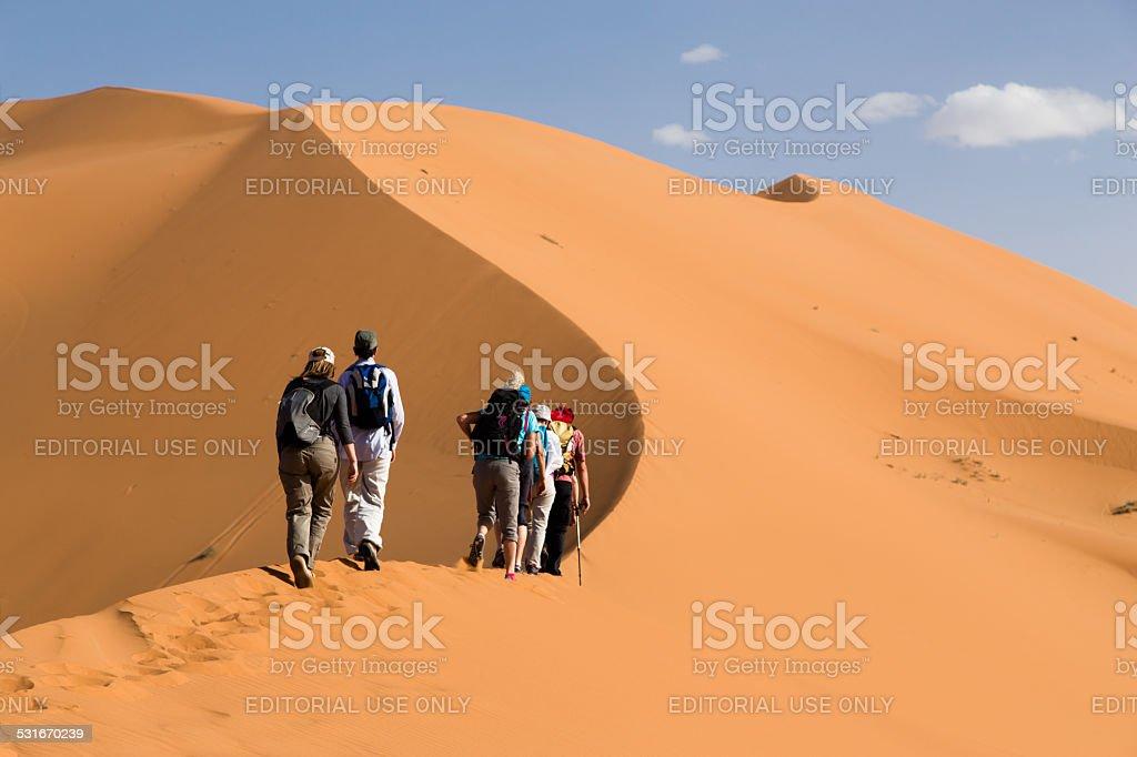 Group of people climbing sand dunes stock photo