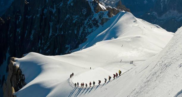 Groupe de personnes d'escalade la montagne recouverte de neige - Photo