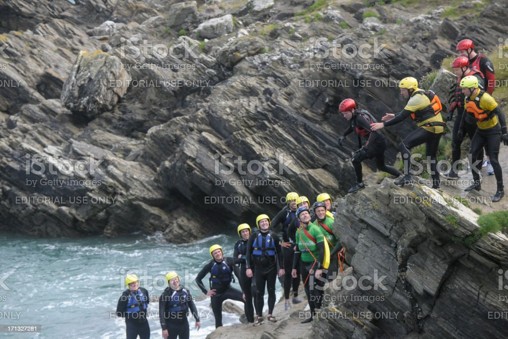 group of people Coasteering on the Cliffs in Newquay, Cornwall. stock photo