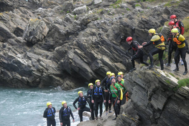 group of people coasteering on the cliffs in newquay, cornwall. - cornwall stock pictures, royalty-free photos & images