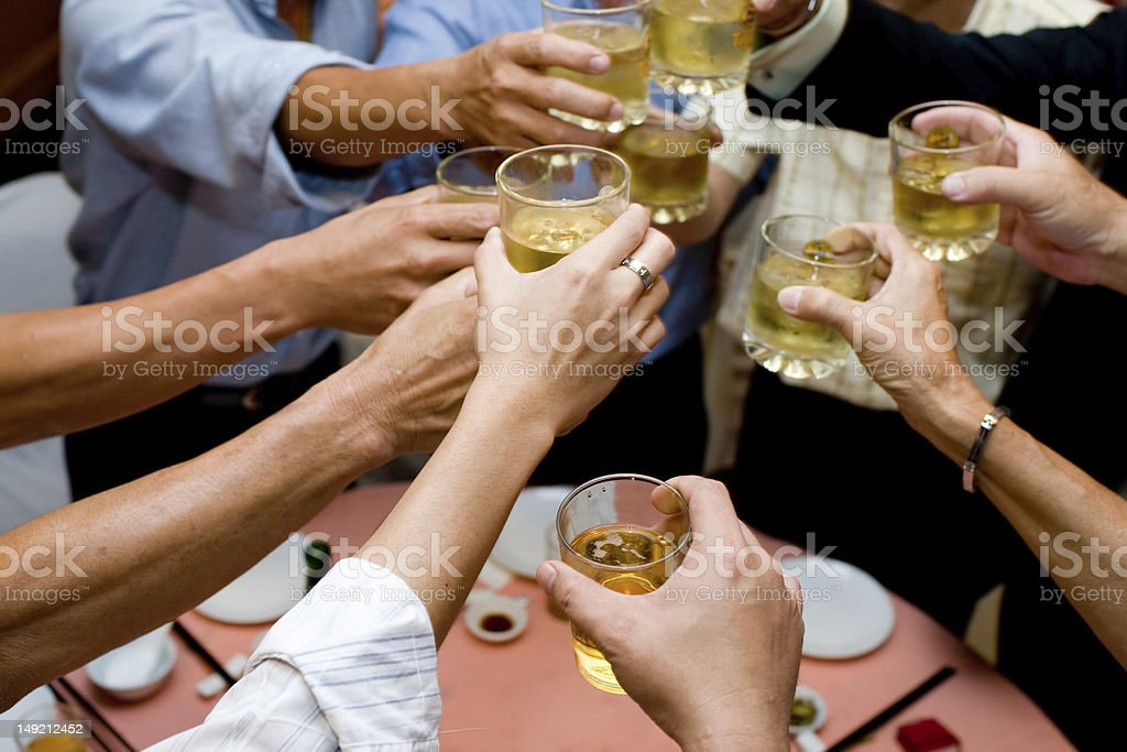 A group of people doing a toast while holding their drinks royalty-free stock photo