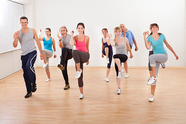 group of people doing aerobics exercises - aerobics stock photos and pictures