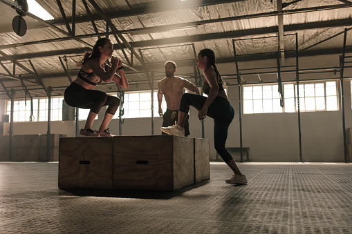 istock Group of people doing box jumping workout in gym 915803066