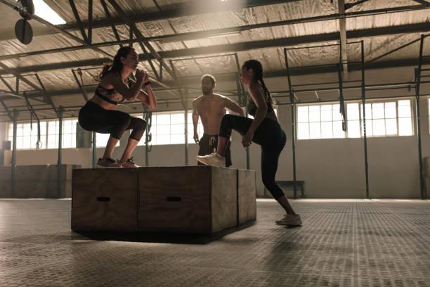 Grupo de personas que hacen caja de salto de entrenamiento en gimnasio - foto de stock