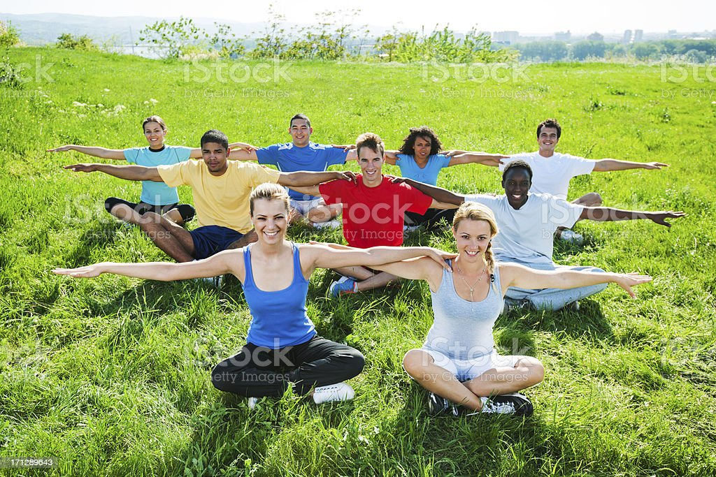 Group of people doing stretching exercises in field. Large group of people exercising together in nature. Activity Stock Photo