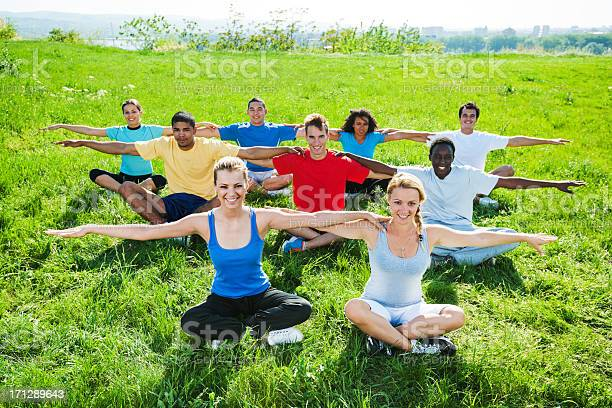 Group Of People Doing Stretching Exercises In Field Stock Photo - Download Image Now