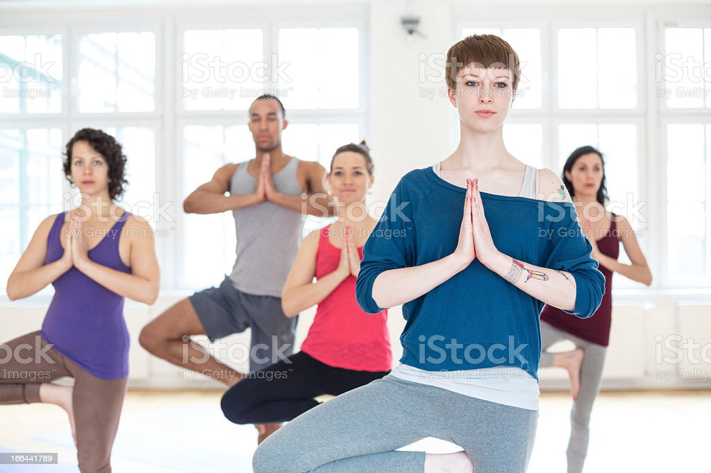 Group of people doing the yoga tree position royalty-free stock photo