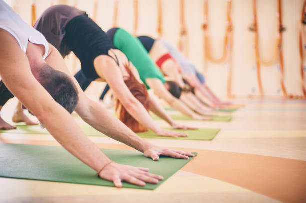 Group of people doing yoga downward facing dog pose on mats at studio stock photo