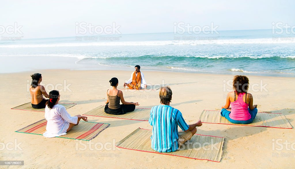 Group of People Doing Yoga on Beach royalty-free stock photo