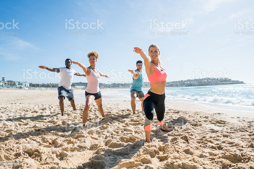 Group of people doing yoga outdoors stock photo