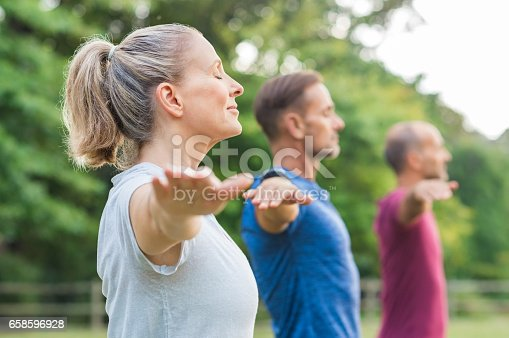 istock Group of people doing yoga 658596928