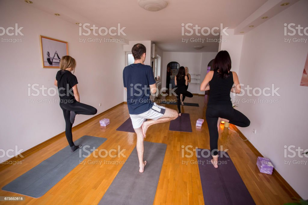 Group of people doing yoga together in class royalty-free stock photo