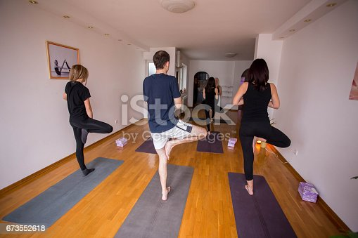 istock Group of people doing yoga together in class 673552618