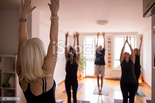 istock Group of people doing yoga together 673552518