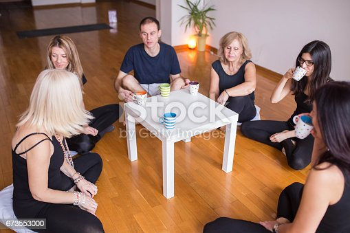 istock Group of people drinking tea after class of yoga 673553000