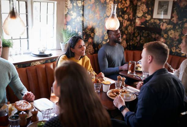 gruppe von menschen essen im restaurant von belebten traditionellen englischen pub - liebeskummer englisch stock-fotos und bilder