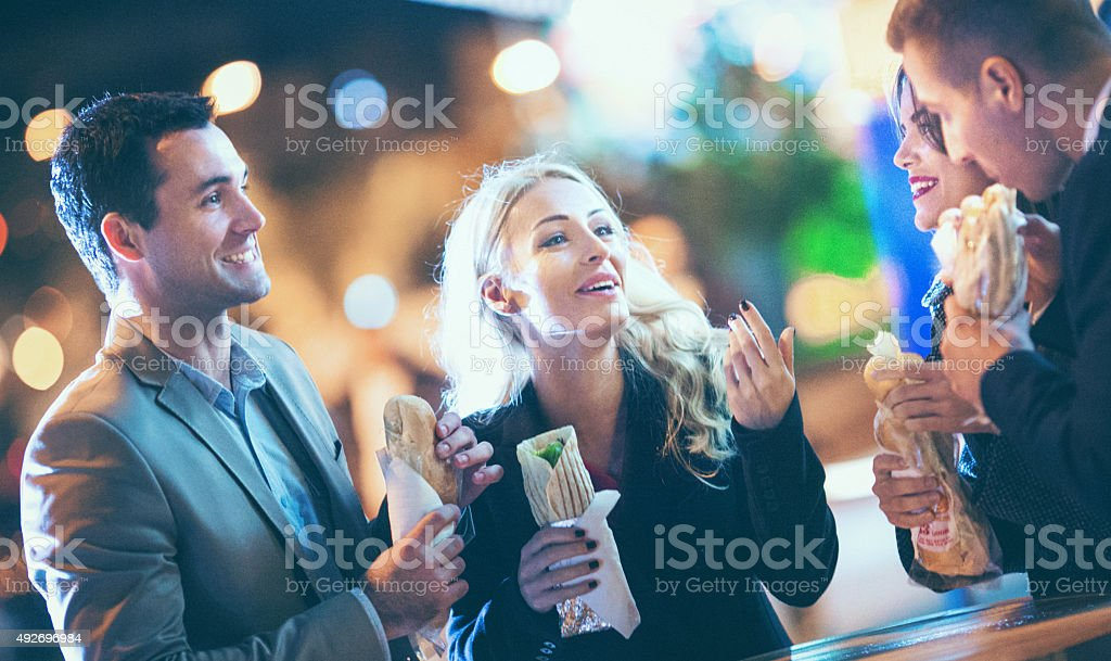 Group of people eating outdoors. stock photo