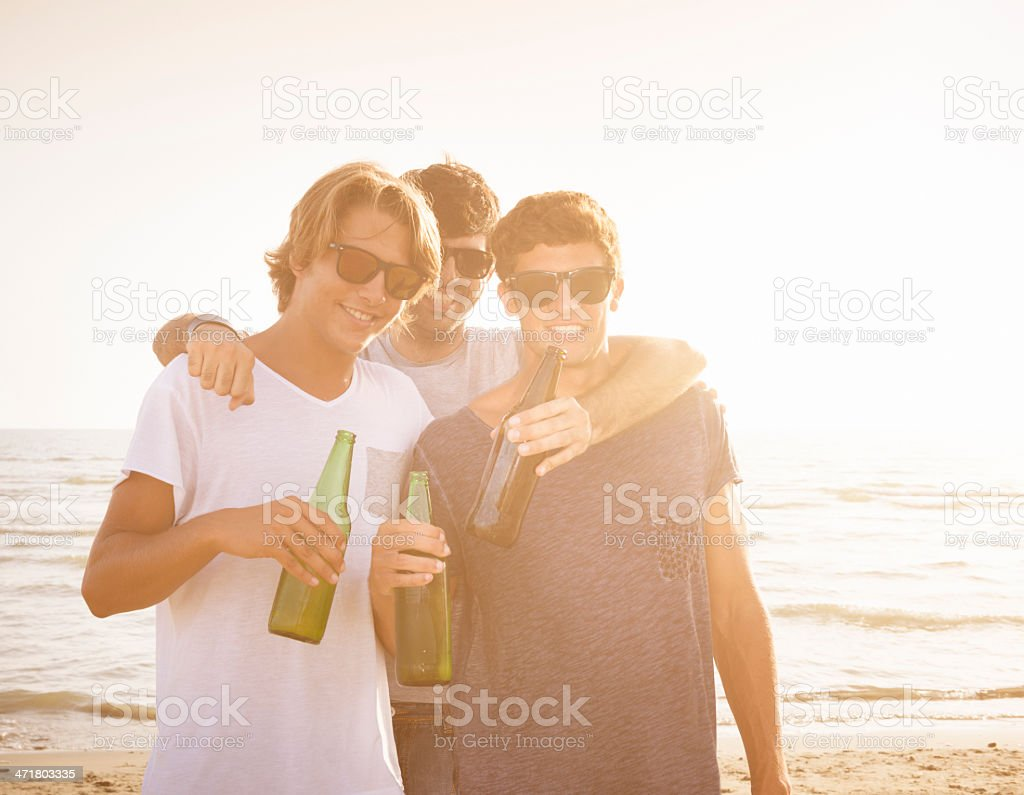 group of people embracing at sunset with beers royalty-free stock photo