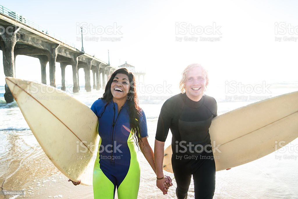 group of people embracing at sunset with surfboard stock photo
