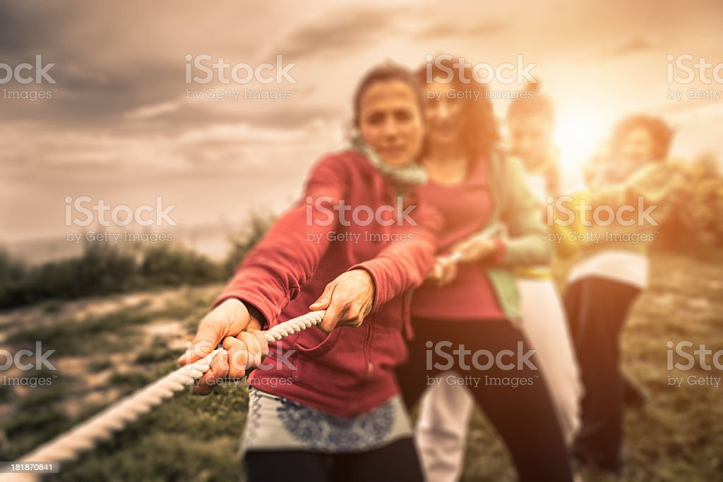 Group of people engaging in tug of war stock photo