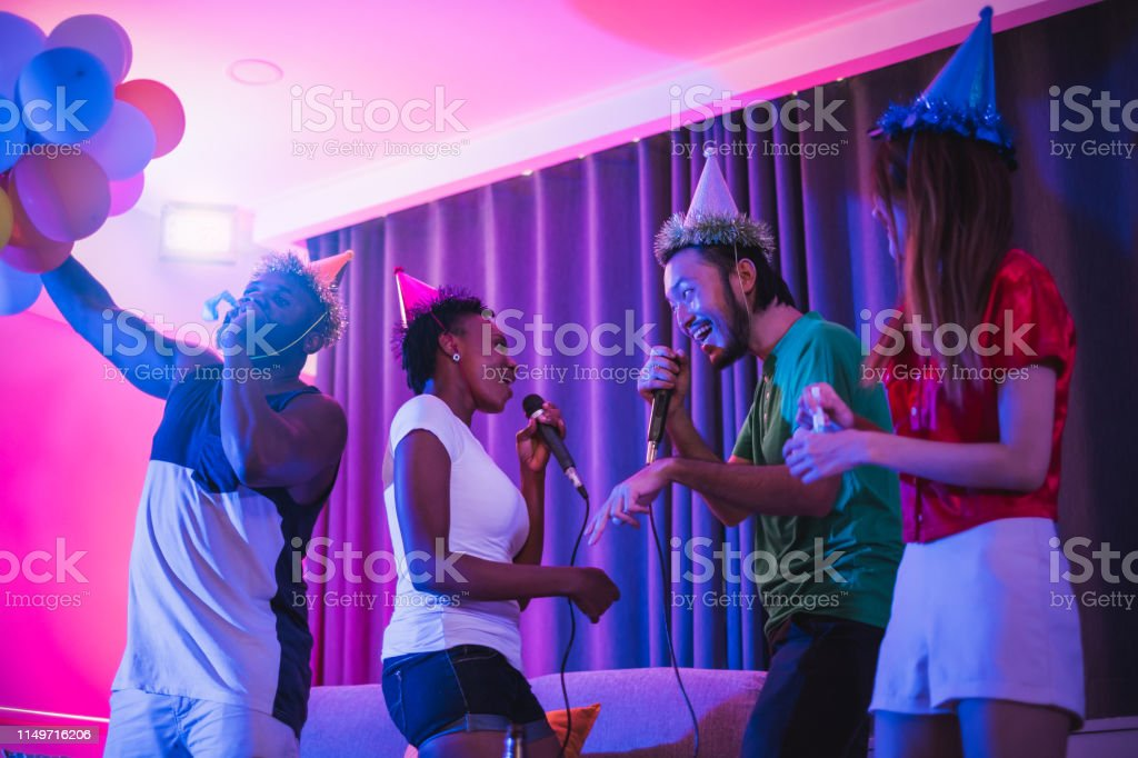 Group Of People Enjoy Night Glow Disco Party Singing Songs