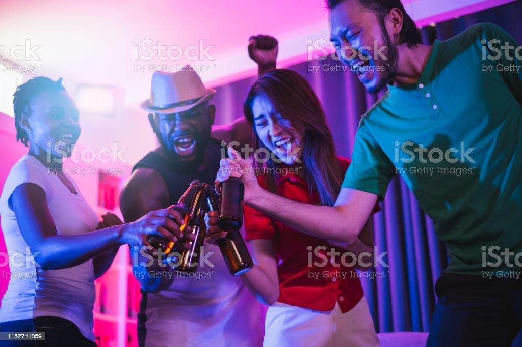 Group Of People Enjoy Night Glow Disco Party Singing Songs Dancing