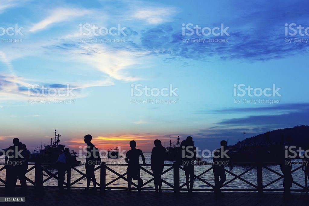 Group of People Enjoying Sunset on the Ocean stock photo