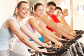 Medium group of young people cycling in modern gym.