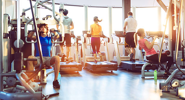 group of people exercise in a gym. - exercise equipment stock photos and pictures