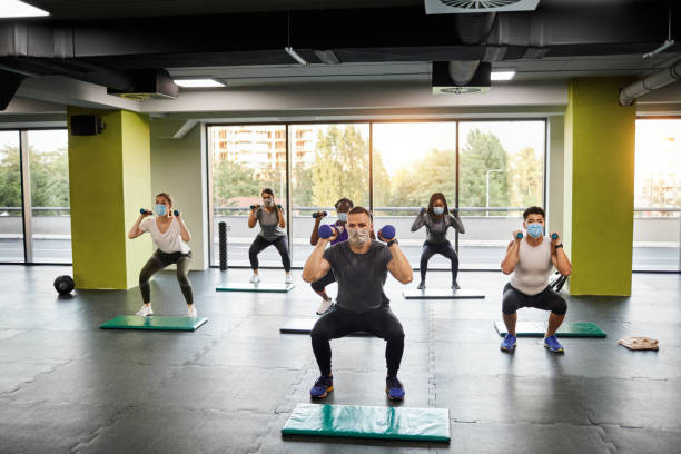 Group Of People Exercising With Male Trainer In The Gym - Reopening Business stock photo